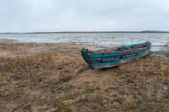 Old wooden boat ashore. With gray sky Stock Photo