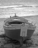 Old wooden boat on beach. Black and white rear view of old wooden boat moored on sandy beach royalty free stock photos