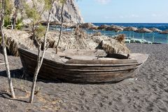 Old wooden boat at the beach. Old wooden boat on black sand at the beach Royalty Free Stock Images