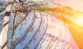 Old wooden boat on the beach. Old paint with cracks. The boat is inverted. Solar glare. stock photography