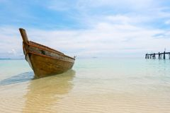Old wooden boat and blue sea under cloudy sky in sunny day. Old wooden boat and blue sea under cloudy sky on white beach in sunny day Royalty Free Stock Photo