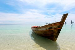 Old wooden boat and blue sea under cloudy sky in sunny day. stock photo