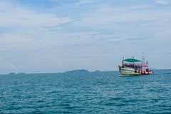 Old wooden boat and blue sea under cloudy sky. Old wooden boat and blue sea under cloudy sky on white beach in sunny day Royalty Free Stock Image