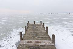 Old wooden boat dock on frozen lake. Old wooden boat dock on the frozen Lake Neusiedl in Weiden with some snow on the ice surface and people ice skating on the Royalty Free Stock Photo