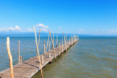 Old wooden boat dock, going far out to sea. Royalty Free Stock Images