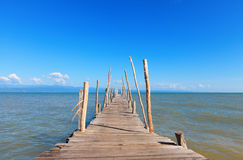 Old wooden boat dock, going far out to sea. Royalty Free Stock Photo
