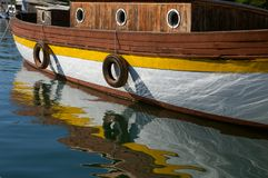 Old wooden boat and its reflection in a water. Detail of old, wooden boat with portholes and its reflection in a wavy sea water surface royalty free stock photos