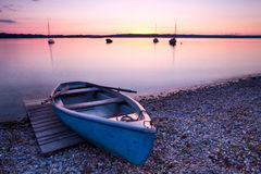 Old wooden boat on lake. Amazing soft pink sunset on lake with old wooden boat royalty free stock images