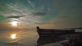 Old wooden boat on lake in sunset summer scene