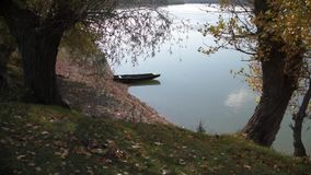 Old wooden boat on lake water near tree. Old boat moored on the river near the tree stock video