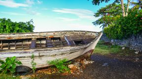 An old wooden boat lying on beach. In Mauritius Islands Royalty Free Stock Image