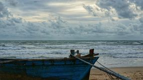 Old wooden boat lying on beach, tied down with rope Royalty Free Stock Photo