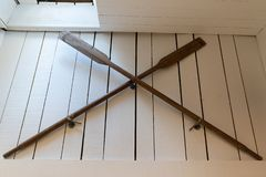 Old wooden boat oars paddle on white wall decoration stock image