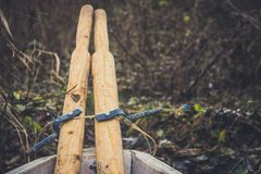An old wooden boat with oars, rope and other gear. Closed oars.  Stock Photography