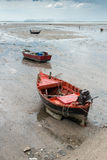 Old wooden boat. Old wooden orange boat tied up at low tide Stock Image