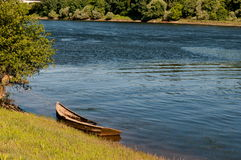 Old wooden boat by the river. Very old and damaged wooden boat at the river Mino side, in Salvaterra, Pontevedra, Spain Royalty Free Stock Photo