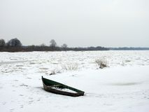 Old wooden boat on river coast in winter, Lithuania Stock Photo