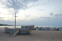 Old wooden boat on a sandy beach on the stony shore royalty free stock photos