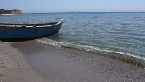 Old wooden boat on the seashore. Old blue wooden boat on the seashore and small waves stock video footage