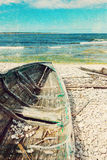 Old wooden boat on the seashore, retro image Stock Photos