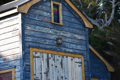 Old wooden boat shed. With peeling blue paint royalty free stock images