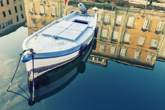 Old wooden boat, sky and ancient historical and building with reflection on blue water Royalty Free Stock Image