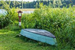 Old wooden boat stored on the lakes shore. In lowland region of Lithuania Stock Photos