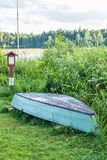 Old wooden boat stored on the lakes shore. In lowland region of Lithuania Royalty Free Stock Photo