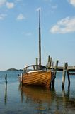 Old wooden boat tied to the jetty. An old classic in good shape tied to its jetty on a warm summer's day on the Swedish west coast Royalty Free Stock Photography