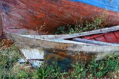 Old Wooden Boats. Detail of two old wooden clinker fishing boats with flaking and faded paint, abandoned in weeds, Greece Stock Photo