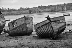 Old wooden boats in a muddty estuary stock photo