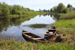 Old wooden boats at the river. Rustic wooden boats at the bank of a small river in the countryside Stock Photos