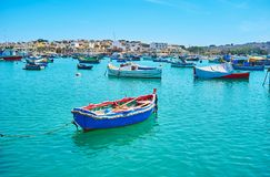 Wooden boats and traditional luzzu vessels, Marsaxlokk. The old wooden boats and traditional luzzu vessels attract tourists to visit Marsaxlokk village and enjoy stock photography