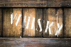 Old wooden box containing bottles of whiskey. royalty free stock image