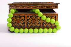 Old wooden box  and round beads. Old wooden box inlaid with green and round beads Royalty Free Stock Photos