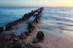 Old wooden breakwater in North sea at sunset Stock Image