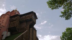 Old Wooden Brick Church. Ancient orange bricks and wood log building fortress temple blue sky clouds tree green leaves historical cultural religion place stock footage