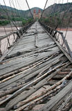 Old wooden bridge. Old wooden foot bridge over the river, with two towers on other side. Bolivia Royalty Free Stock Photos