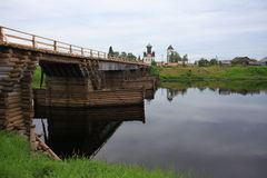 Old wooden bridge across the river. North Russia Stock Photo