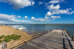 Old wooden bridge on the bay and the boats on the water. Stock Image