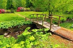 Old wooden bridge in a beautiful garden Stock Images