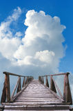 Old wooden bridge, blue sky and white clouds Stock Image