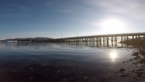 Old wooden bridge and calm waves and bright sunshine in northern norway