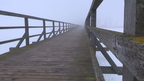 Old wooden bridge mystical perspective in morning mist stock footage