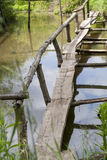 Old wooden bridge over the lake overgrown with grass Stock Photos