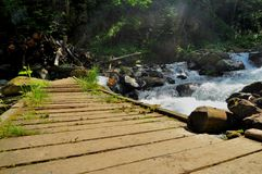 Old wooden bridge over a mountain stream Royalty Free Stock Photo