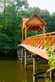 Old wooden bridge over the river with arbor. Forest River. royalty free stock photos