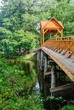 Old wooden bridge over the river with arbor. Forest River. stock photos