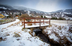 Old wooden bridge over river in Austrian Alps Royalty Free Stock Photo