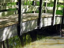 Old wooden bridge over river. Closeup of old wooden bridge over river in countryside Royalty Free Stock Images